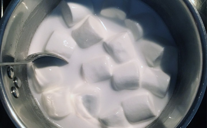 Marshmallows melting into 7-Up in a pot.