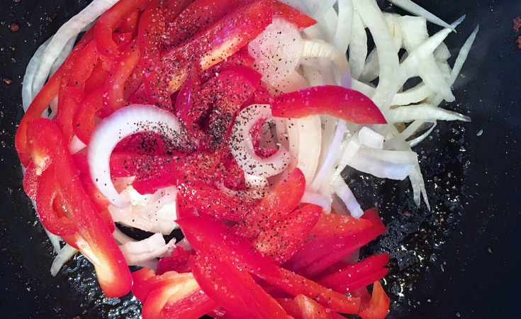 Sliced yellow onions and red bell peppers seasoned with salt and pepper in a skillet.