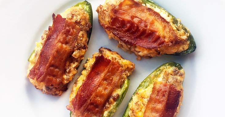 Four maple sausage cream cheese jalapeno poppers with bacon on a white plate.