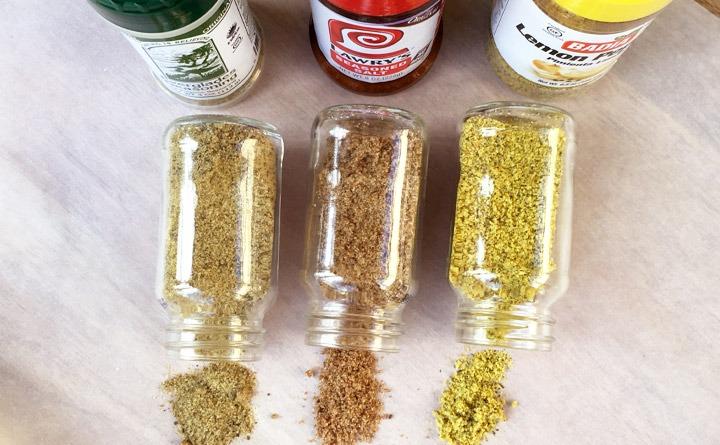 Cowboy Dust ingredients in glass seasoning jars: Everglades Seasoning, Lawry's Seasoned Salt and Lemon Pepper.