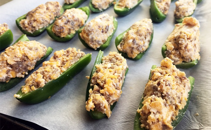 Jalapeno slices stuffed with maple sausage, cream cheese, sharp cheddar on a baking sheet.