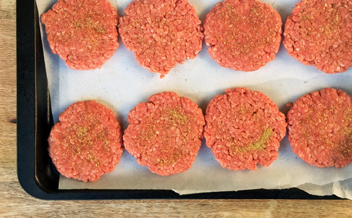 Smashburger Slider ground beef patties on a baking sheet sprinkled with Cowboy Dust Everything Seasoning.