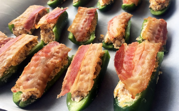 Jalapeno halves stuffed with maple sausage, cream cheese, and cheddar cheese on baking sheet.