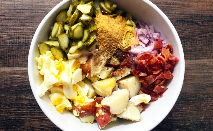 Ingredients for dill potato salad: dill pickles, eggs, bacon, red onion, mayo, mustard and spices.