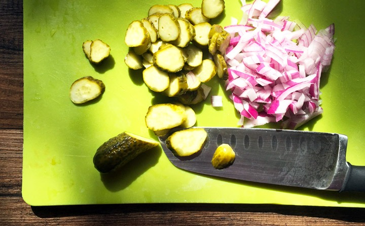 Sliced Claussen baby dill pickles and red onions for Dill Potato Salad.